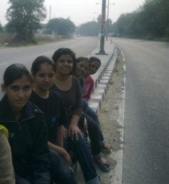 Staring deadpan into the camera while posing on the divider of the highway infront of the college - yes!