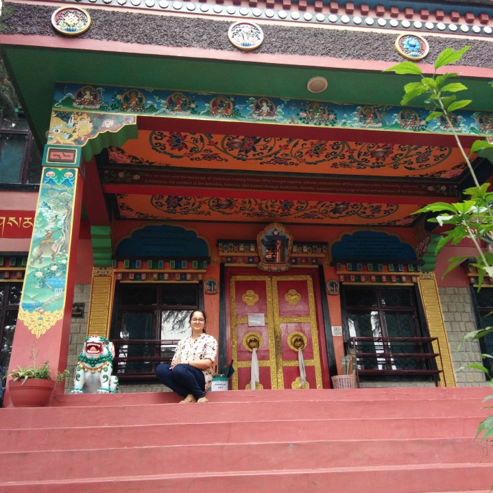 Sitting on the steps to the entrance of the gompa. The pillars and ceiling have paintings of Buddhist themes and sayings